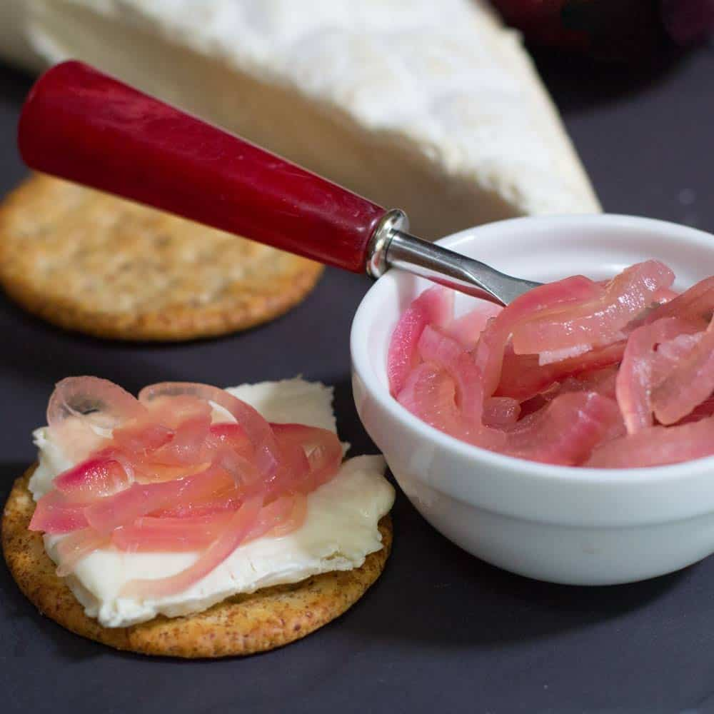 pickled onions in ramekin and on cracker with wedge of brie
