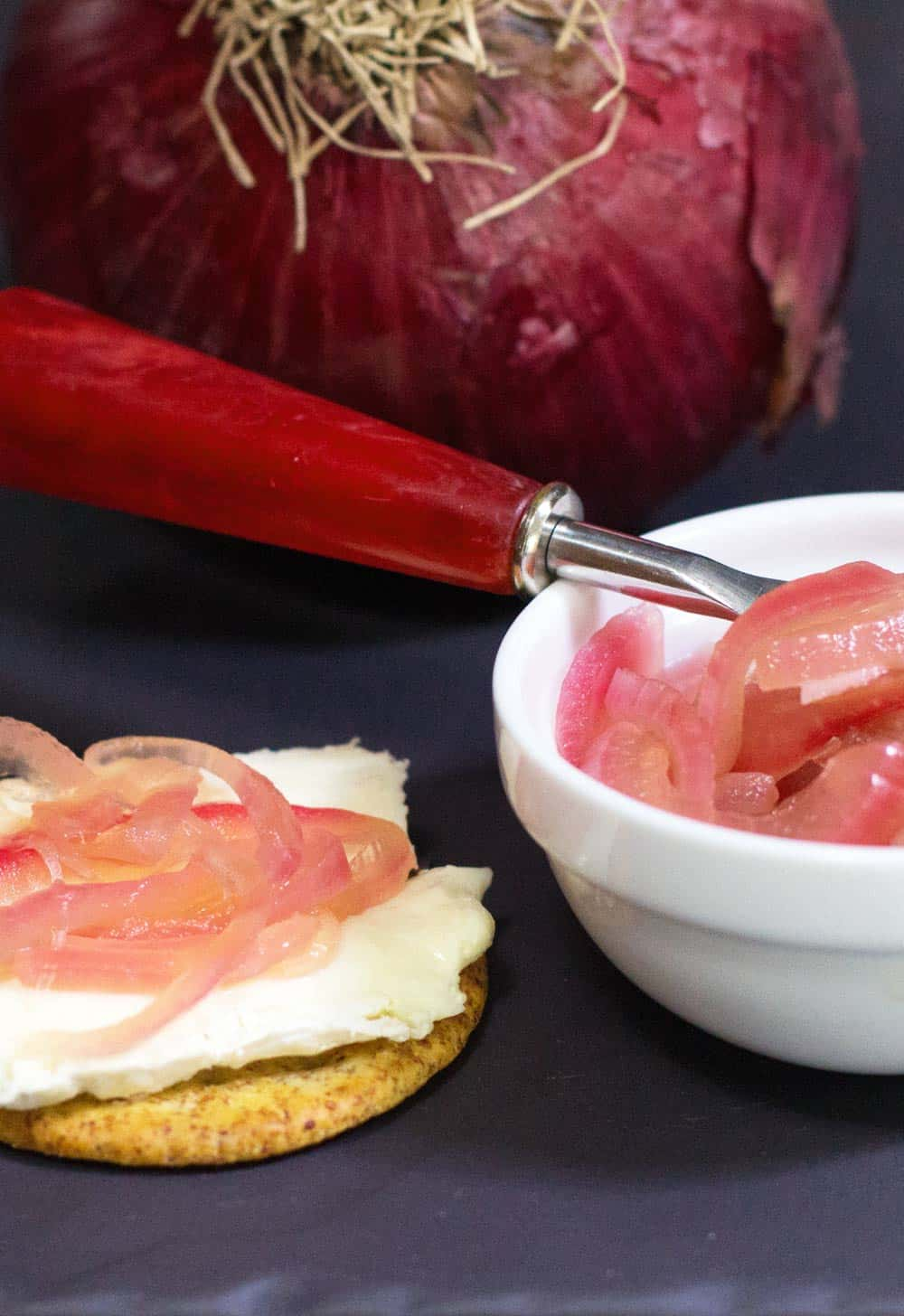 Pickled onions on brie with red onion in background