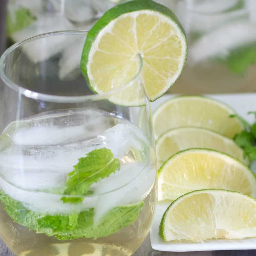 Hugo cocktail with a plate of lime and mint