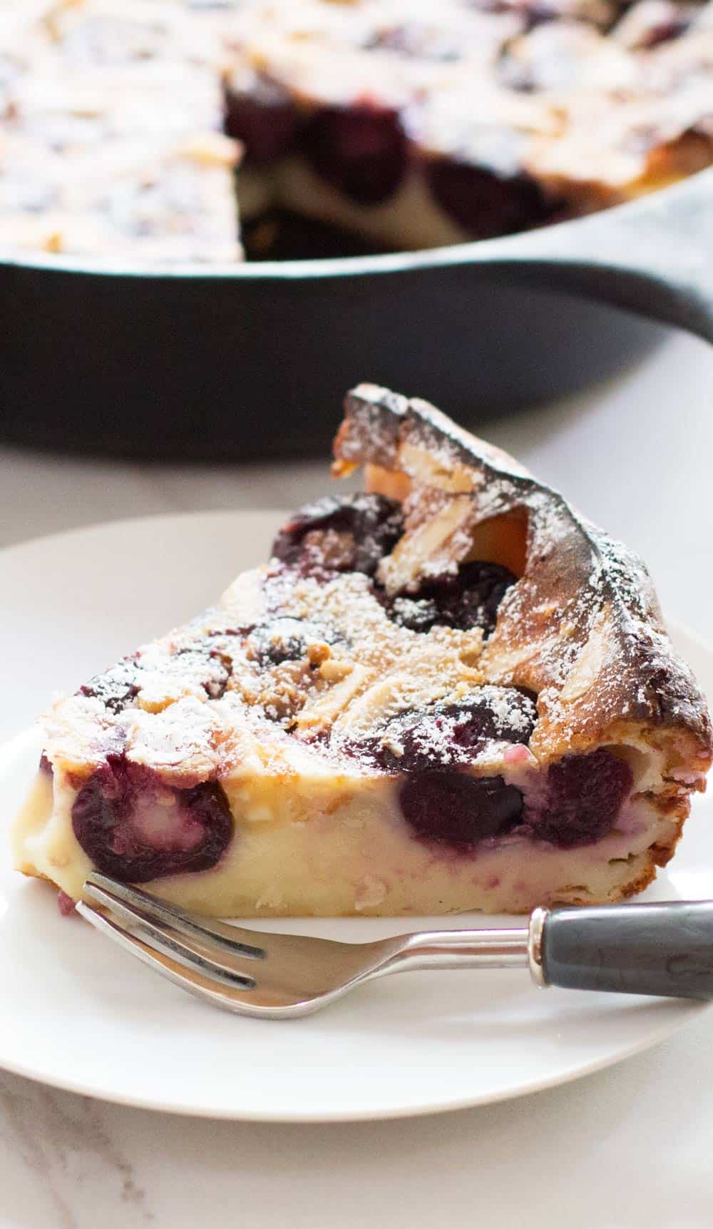 piece of cherry clafoutis with pan in background