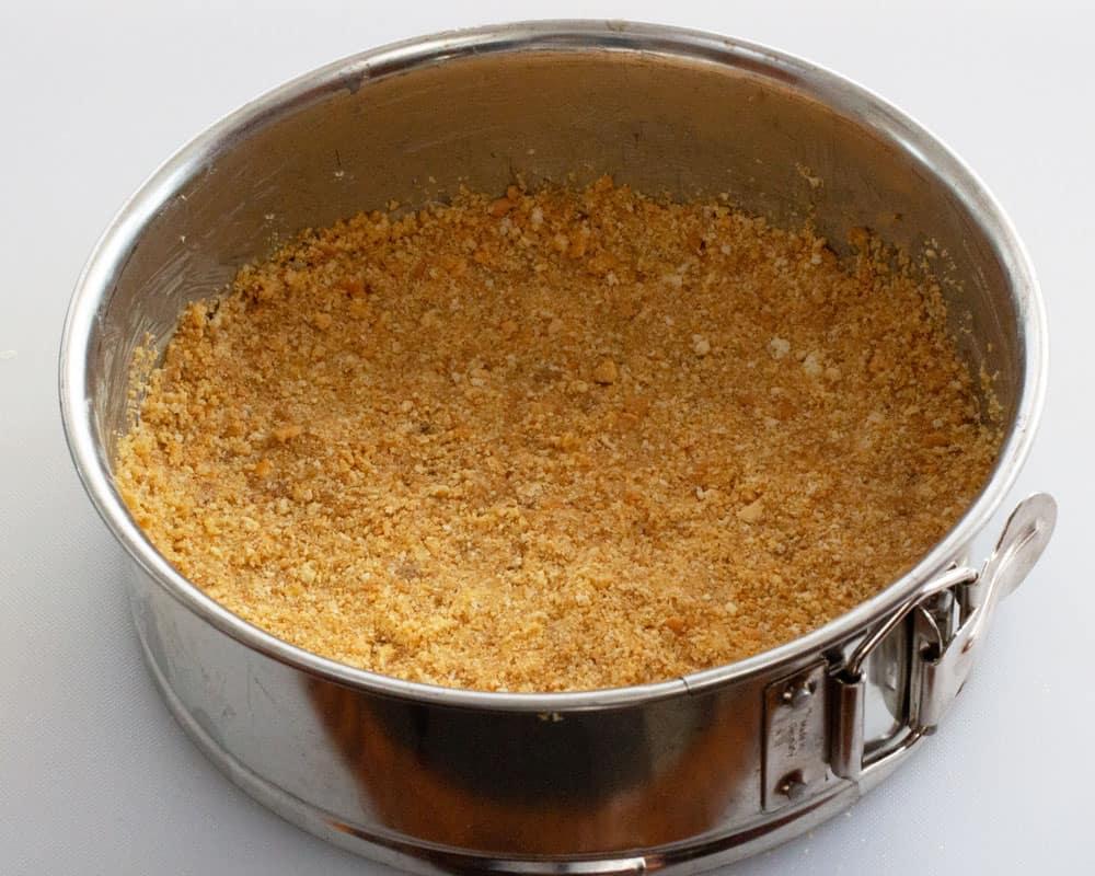 Pressing mixed crumbs into springform pan for no-bake lemon mascarpone cheesecake