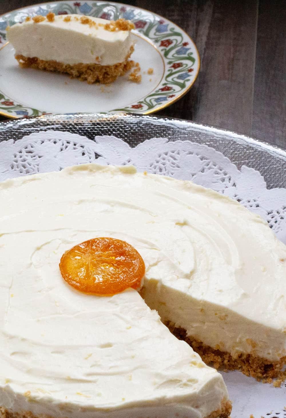 vertical shot of no-bake lemon mascarpone cheesecake with a slice behind.