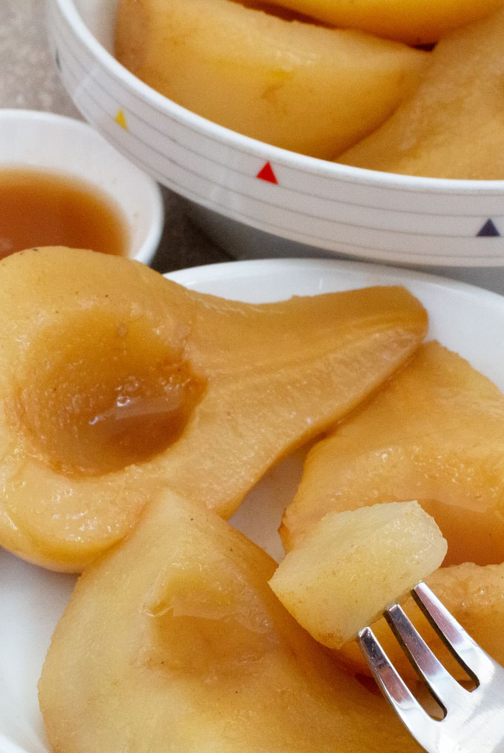 A piece of a Cider Masala Poached Pear above a plate of pears