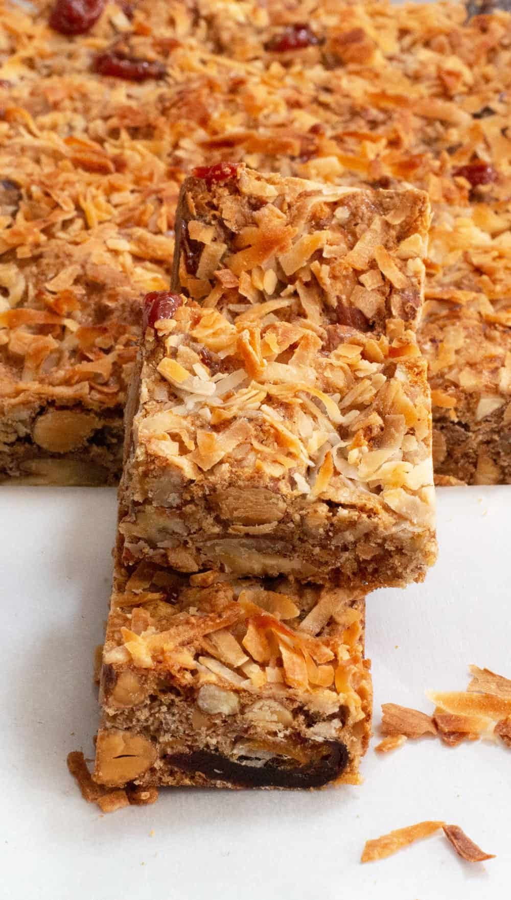 coconut-topped dried fruit & nut bars stacked with rest of batch behind