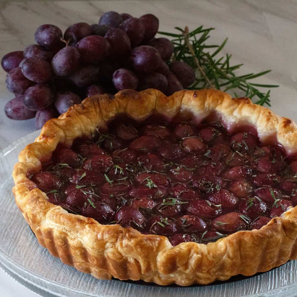 Roasted red grape and rosemary tart with bunch of grapes and fresh rosemary in background