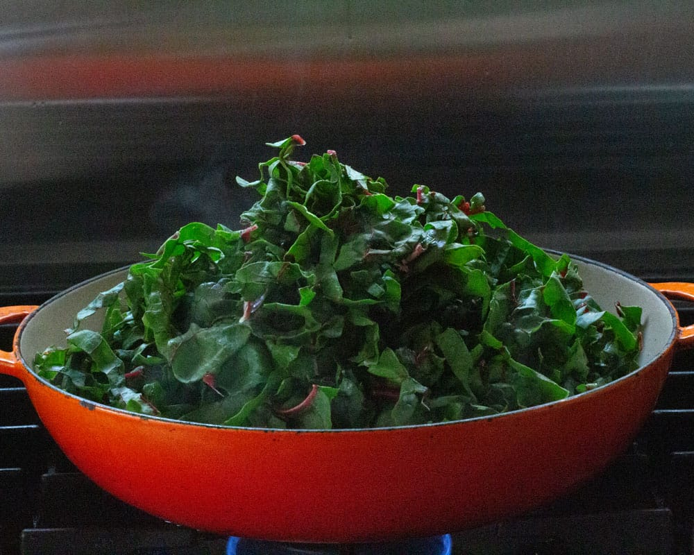 pile of Swiss chard leaves added to onions, stems and spices