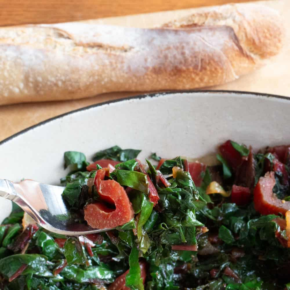 Swiss chard on fork with baguette in background