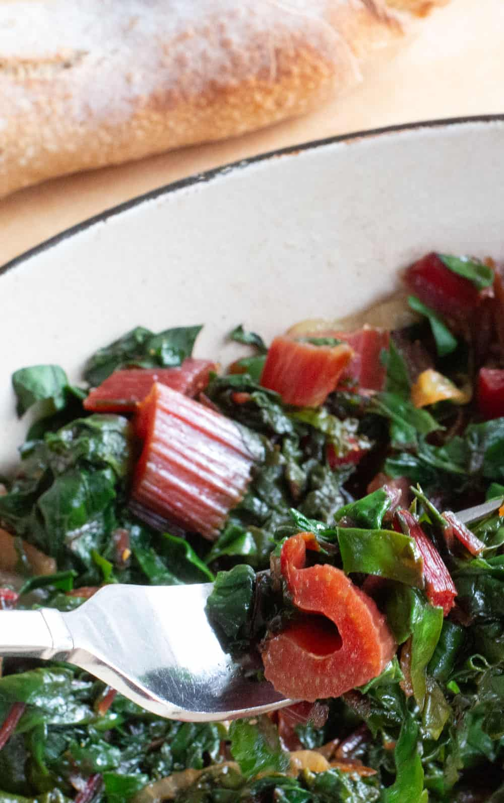 Swiss chard finished cooking with baguette in background