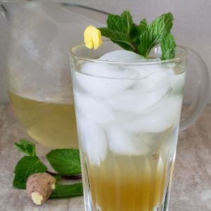 ginger mint agave soda in a glass with pitcher behind