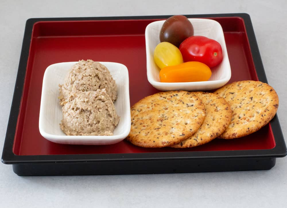 a tray of vegetarian chopped liver with lentils, crackers and tomatoes