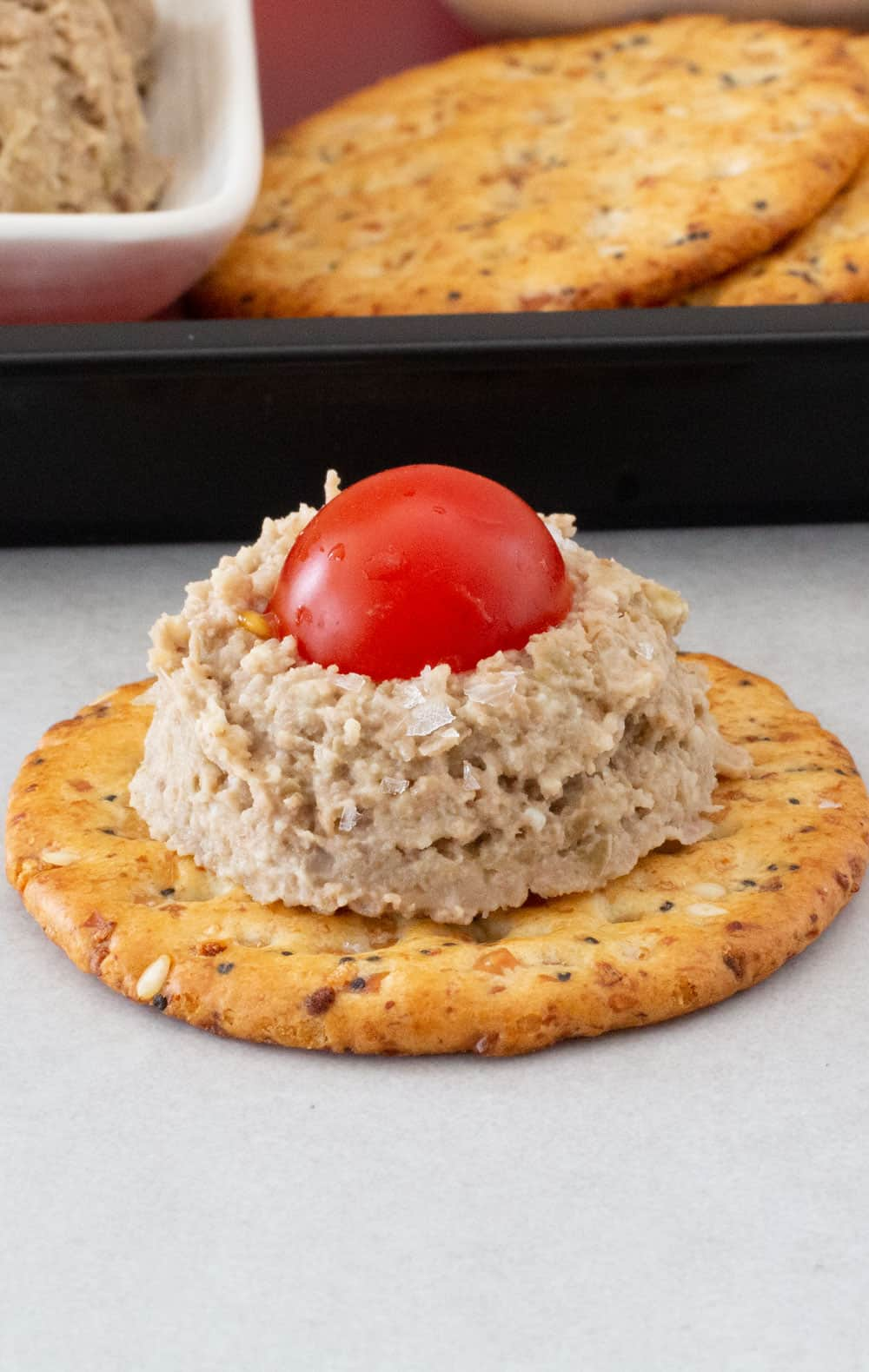 vegetarian chopped liver with lentils on a cracker in front of crackers and spreadarian cho