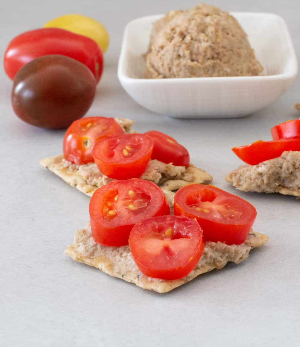 vegetarian chopped liver with lentils on crackers with extra tomatoes and a ramekin of spread in background