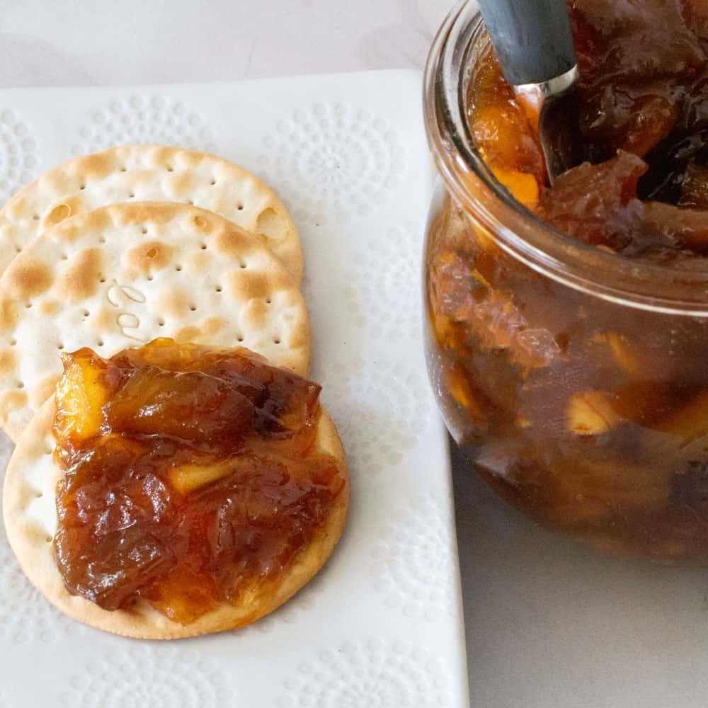 a cracker with rhubarb ginger jam and a pot of jam next to it