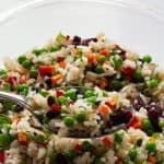 confetti rice vegetable salad on a spoon with bowl of salad in background