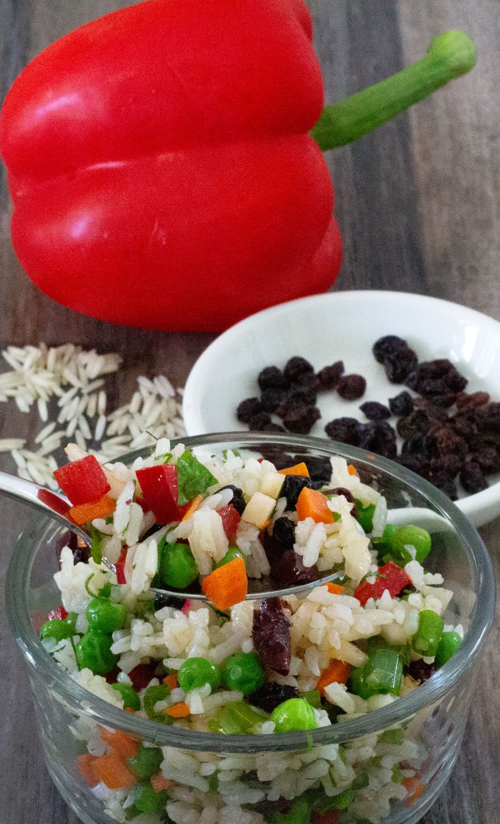 confetti rice vegetable salad with rice, currants and a red pepper in background