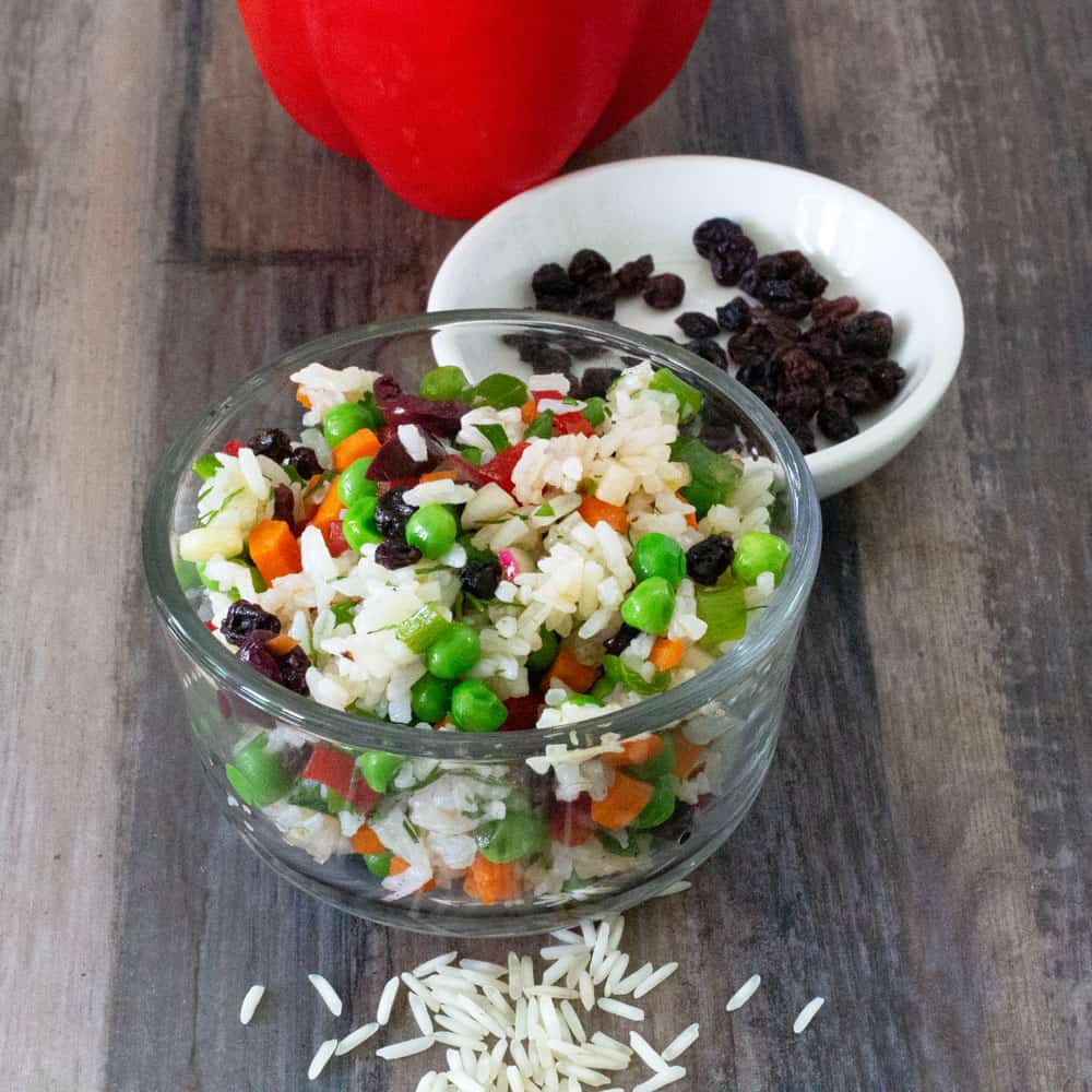 bowl of summer confetti rice vegetable salad with ingredients spread around it