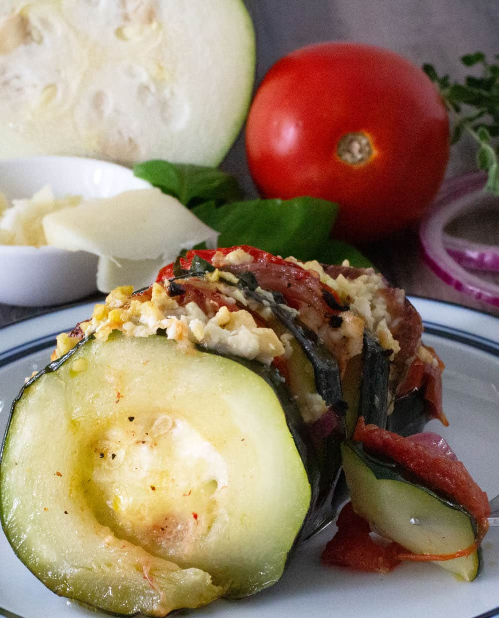 hasselback zucchini with cheese and vegetables in background