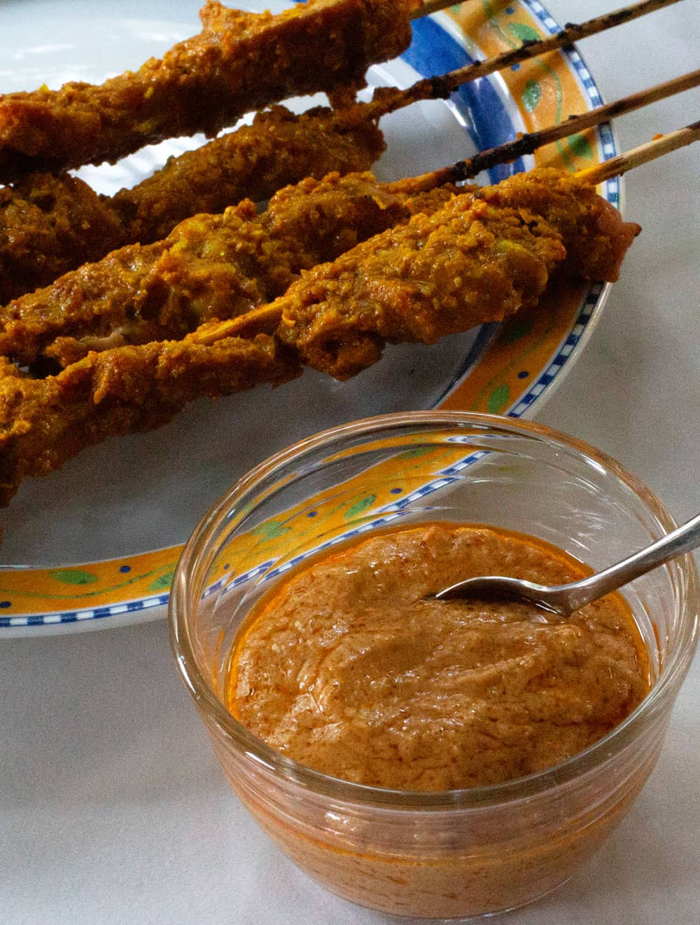 peanut curry sauce with satay in the background