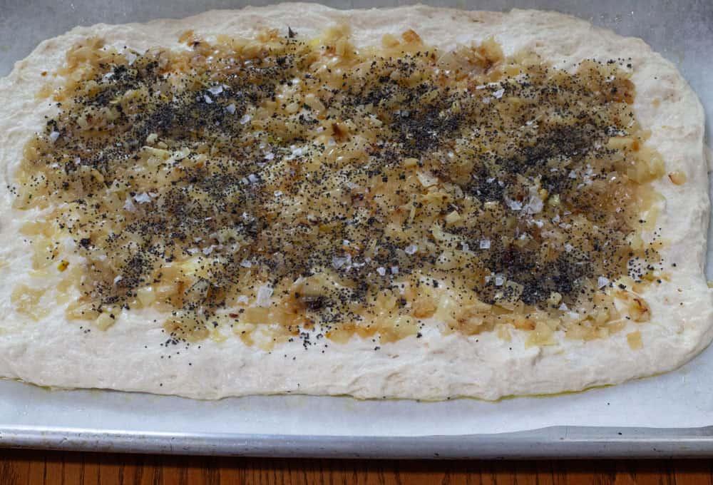 poppy seed and flake salt on pletzel dough before baking