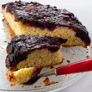 piece of blueberry ginger cornmeal cake on fork with cake in background